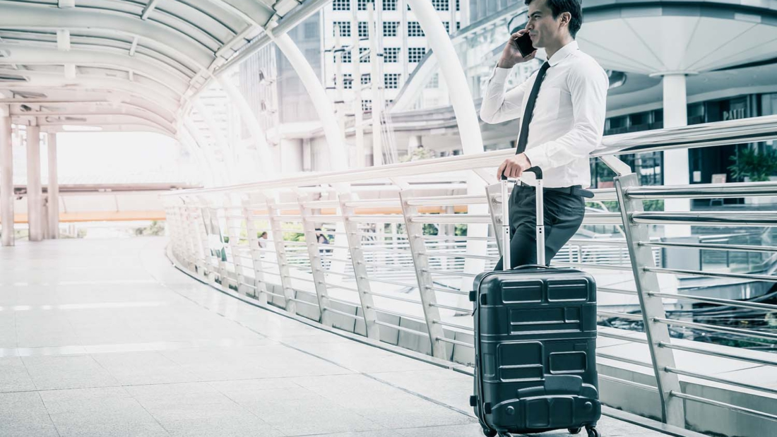 Business man stading with Luggage and mobile phone Business Trip concept