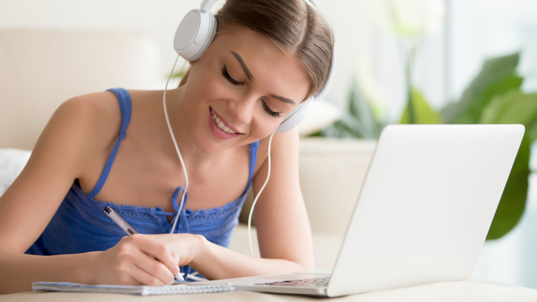 Smiling teen girl wearing headphones listening to audio course using laptop at home, making notes, young woman learning foreign languages, digital self education, studying online, enjoying music
