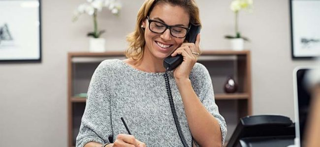 Beautiful mature woman talking on phone at creative office. Happy smiling businesswoman answering telephone at office desk. Casual business woman sitting at desk making telephone call and taking note.